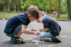 Les frères jumeaux dessinent sur la route avec la craie Photos stock