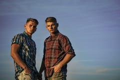 Les frères sont des jumeaux Le concept de la vie en dehors de la ville Hommes ou bodybuilders jumeaux dehors sur le ciel bleu Image libre de droits