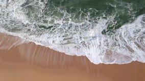 Les frais généraux élevés aériens ondulent la rupture sur la plage avec le sable d'or et le vert/mer bleue au Portugal banque de vidéos