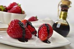 Les fraises avec du vinaigre balsamique se laisse tomber derrière avec les fraises entières Photo libre de droits