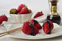 Les fraises avec du vinaigre balsamique se laisse tomber derrière avec les fraises entières Photographie stock