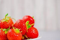 Les fraises dans la cuvette sur la table en bois avec discret et la copie spacen Photos libres de droits