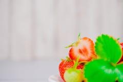 Les fraises dans la cuvette sur la table en bois avec discret et la copie spacen Photo libre de droits
