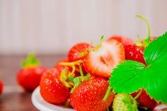 Les fraises dans la cuvette sur la table en bois avec discret et la copie spacen Images libres de droits