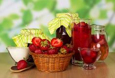 Les fraises de panier, cuillère, pots bloquent, les boissons, crème sur le vert abstrait Photo stock
