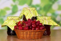Les fraises de panier, les framboises et les cerises, pots bloquent sur le vert abstrait Photo libre de droits