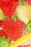 Les fraises et les citrons nagent dans l'eau de scintillement Photographie stock libre de droits