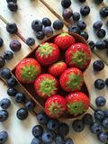 Les fraises et les myrtilles fraîches dans le foyer forment le panier Image stock
