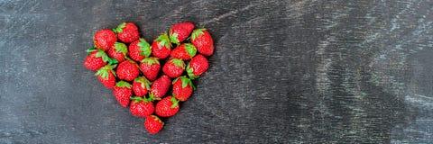 Les fraises fraîches de BANNIÈRE rangent la forme de coeur sur le long format de vieux fond en bois Photographie stock