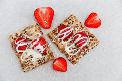 Les fraises fraîches rouges sont sur le biscuit avec des grains, lait doux Photographie stock libre de droits
