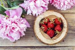 Les fraises mûres à un coeur ont découpé dans le bois avec le péon rose Photo stock