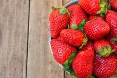 Les fraises organiques mûres dans la cuvette en céramique bleue sur le fond en bois de planche, se ferment, nourriture saine, net Photos stock