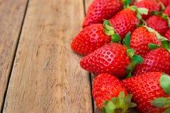 Les fraises organiques mûres dispersées sur le fond en bois de planche, se ferment, angle faible, nourriture saine, nettoyant Image stock
