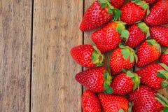 Les fraises organiques mûres ont dispersé sur le fond en bois de planche, nourriture saine, nettoyant, régime, vue supérieure Photos libres de droits