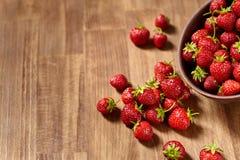 Les fraises rouges fraîches dans un argile brun roulent sur la table en bois Photographie stock libre de droits
