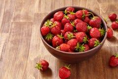 Les fraises rouges fraîches dans un argile brun roulent sur la table en bois Image libre de droits