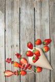 Les fraises rouges fraîches entières ont dispersé du cône de papier et ont coupé en tranches des fraises sur les brochettes en bo Images libres de droits