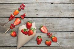 Les fraises rouges fraîches entières ont dispersé du cône de papier et ont coupé en tranches des fraises sur les brochettes en bo Photos stock