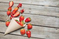 Les fraises rouges fraîches entières ont dispersé du cône de papier et ont coupé en tranches des fraises sur les brochettes en bo Image stock
