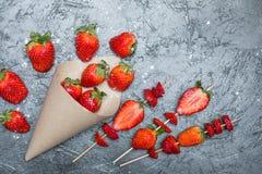 Les fraises rouges fraîches entières ont dispersé du cône de papier et ont coupé en tranches des fraises sur les brochettes en bo Image libre de droits