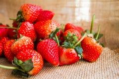 Les fraises rouges fraîches ont arrangé sur un sac, qui est à l'arrière-plan Photo stock