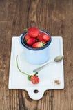 Les fraises rouges mûres fraîches dans l'émail bleu attaquent sur le conseil en céramique blanc au-dessus du fond en bois rustiqu Images stock