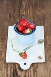 Les fraises rouges mûres fraîches dans l'émail bleu attaquent sur le conseil en céramique blanc au-dessus du fond en bois rustiqu Photo stock