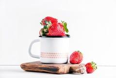 Les fraises rouges mûres fraîches dans l'émail de style campagnard attaquent sur le conseil en bois rustique au-dessus du fond bl Photo libre de droits