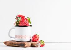 Les fraises rouges mûres fraîches dans l'émail de style campagnard attaquent sur le conseil en bois rustique au-dessus du fond bl Image stock