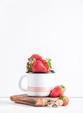 Les fraises rouges mûres fraîches dans l'émail de style campagnard attaquent sur le conseil en bois rustique au-dessus du fond bl Photo stock