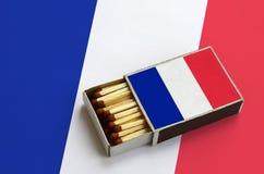 Les Frances diminuent sont montrées dans une boîte d'allumettes ouverte, qui est remplie de matchs et se trouve sur un grand drap images stock