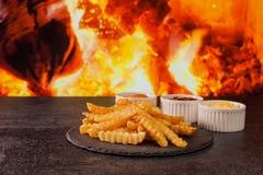 Les fritures délicieuses ont servi avec la variété de trois sauces devant la cheminée image libre de droits