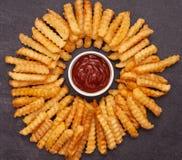 Les fritures ont arrangé en cercle autour du bol de ketchup images libres de droits