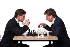 Les frères jumeaux jouant des échecs d'isolement sur le blanc Images stock