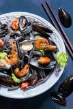 Les fruits de mer avec les pâtes, les moules, la crevette et les légumes noirs photo libre de droits