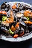 Les fruits de mer avec les pâtes, les moules, la crevette et les légumes noirs photographie stock