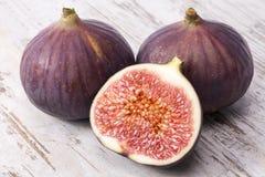 Les fruits des figues fraîches entières et demi sur la planche en bois, se ferment  Images stock