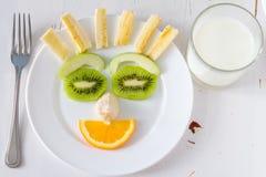 Les fruits et légumes se sont chargés de sembler attrayants aux enfants dans le visage drôle Image libre de droits