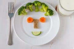 Les fruits et légumes se sont chargés de sembler attrayants aux enfants dans le visage drôle Photographie stock libre de droits