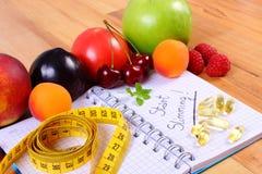 Les fruits, marque sur tablette des suppléments et le centimètre avec le carnet, le régime et la nourriture saine Images libres de droits