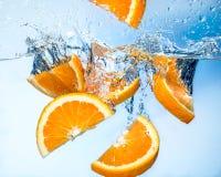Les fruits oranges tombent profondément sous l'eau avec l'éclaboussure Image libre de droits