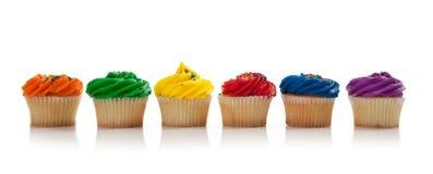 Les gâteaux colorés assortis avec arrose sur le blanc Photos libres de droits