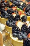 Les gâteaux de fromage ont complété avec des baies en vente dans une pâtisserie locale image stock