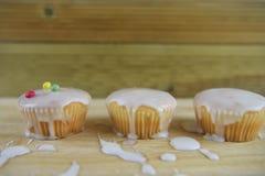 Les gâteaux faits maison glacés et décorés dans un enfant aiment la manière avec le fond en bois malpropre de table Images libres de droits