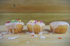 Les gâteaux faits maison glacés et décorés dans un enfant aiment la manière avec le fond en bois malpropre de table Photo stock