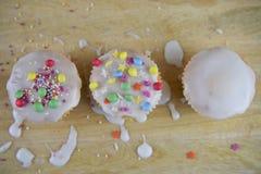 Les gâteaux faits maison glacés et décorés dans un enfant aiment la manière avec le fond en bois malpropre de table Images stock