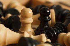 Les gages noirs et blancs de pièces d'échecs ont entouré le plan rapproché Images libres de droits