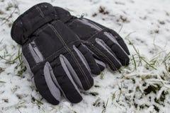 Les gants d'hiver dans la neige, les gants noirs de sport se situent pendant l'hiver dans la neige photo stock