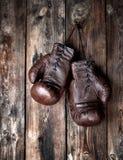 les gants de boxe bruns en cuir tr?s vieux accrochent sur un vieux mur en bois minable photos stock