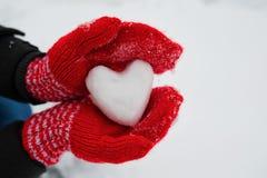 Les gants femelles rouges tiennent un coeur blanc de la neige Photographie stock libre de droits